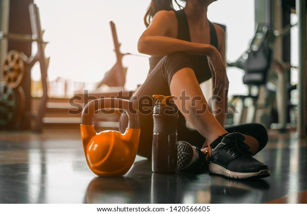 fitness ,workout, gym exercise ,lifestyle  and healthy concept.Fitness woman Relaxing after exercise with a whey protein and dumbbell placed beside the gym.Relaxing after training.