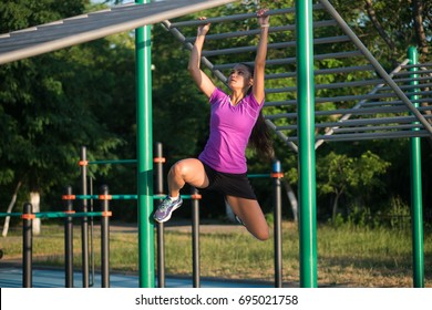 Fitness workout, healthy strong body beautiful young woman, female bodybuilder champion athlete gym, girl performs a pulling up exercise, exercises on horizontal bar,