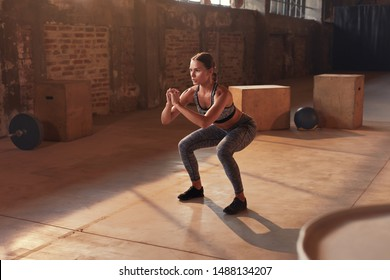 Fitness workout. Sport woman doing squat leg exercise at gym. Beautiful girl athlete with fit body in sportswear exercising, having functional training indoors - Shutterstock ID 1488134207
