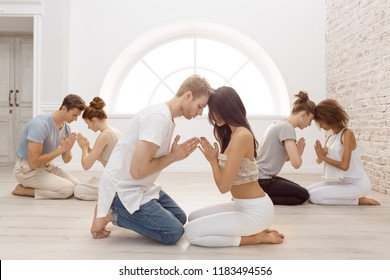 Fitness, yoga and healthy lifestyle concept - group of people doing lotus seal gesture and meditating in seated pose at studio. Group of young multi-ethnic beautiful couples sitting together with