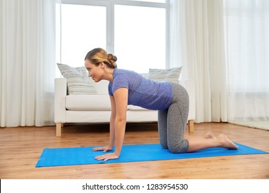 fitness, yoga and healthy lifestyle concept - woman doing cow pose on mats at home