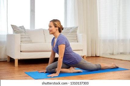 fitness, yoga and healthy lifestyle concept - woman doing swan yin pose on mats at home