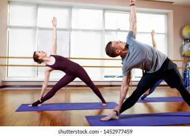 Fitness, yoga and healthy lifestyle concept - a group of people who do exercises for stretching and meditating in various yoga poses.