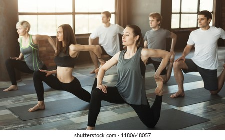 Fitness or yoga practice. Group of fit people working out in sports club, doing warming up exercises, stretching feet, copy space