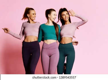 Fitness and yoga sport girls friends in blue, grey, brown train suits walk together, talk and laugh. Workout and yoga girls on pink background.