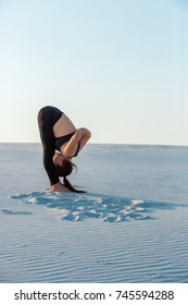 Fitness yoga woman stretching on sand. Fit female athlete doing yoga pose.