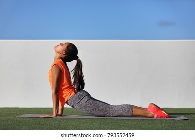 Fitness yoga woman stretching practicing morning sequence doing cobra pose or upward facing dog, bhujangasana. Fit fitness girl stretching summer park grass. Beautiful multiracial female model.