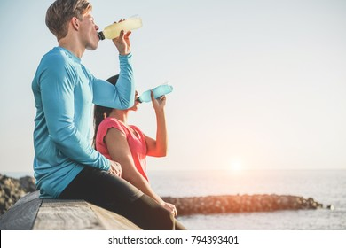 Fitness young couple drinking energy drink outdoor - Sporty people rest and hydrate the body after training workout session - Healthy lifestyle and jogging concept - Focus on man face