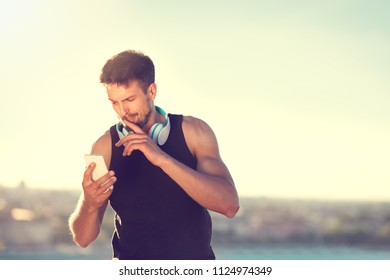 fitness young man concentrated looking at phone during workout