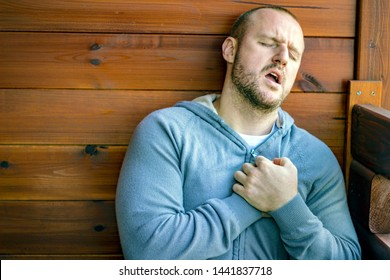 Fitness young man have chest pains or heart attack at home. Close-up of man having heart attack after working hard all day. Man feels strong chest pain. Healthcare and medical concept.