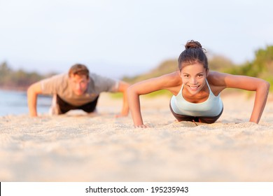 Fitness young people doing pushups on beach. Fit couple, female sport model and man training crossfit outdoors. Multiracial couple, Asian woman Caucasian man athlete in their 20s.