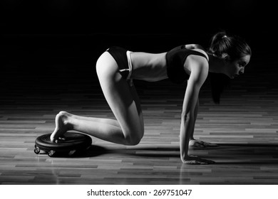 Fitness young sexy girl in the gym doing exercises with abdominals. Sexy young fitness girl pulls up in the gym. Brunette fitness woman in black sport wear with perfect fitness body.