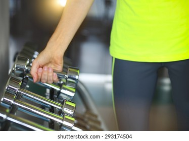 Fitness young woman with barbells on gym background