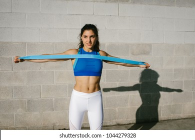 Fitness young woman doing back exercise with resistance band for training strength. Female athete exercising outside.