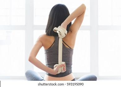 Fitness young woman doing yoga exercise in sportswear with strap near a window in studio, back view. Pilates and stretching concept