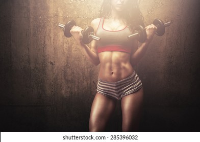 Fitness young woman in hard training building muscles and posing in front of gym wall