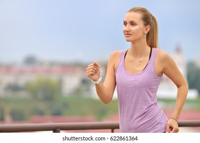 Fitness young woman jogging in the city park. Fitness girl training outdoor