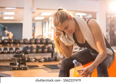 Fitness young woman resting on fitness ball in gym.