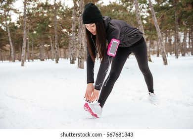 Fitness young woman runner stretching legs before workout outdoors in winter forest