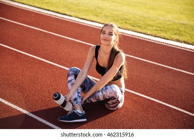 Fitness young woman sitting on running track and holding water bottle at the stadium