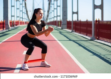 Fitness young woman in sport apparel crouching using resistance band while workout. Space for text