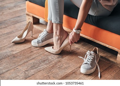 Fits perfect. Close up of young woman trying on elegant shoes with high heels while sitting in the shoe store
