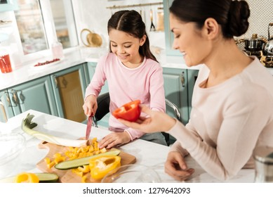 It fits you. Pleased girl keeping smile on her face while doing healthy salad