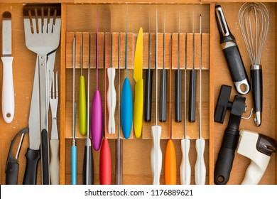 Fitted knife drawer in a wooden kitchen cabinet with a neat array of knives with assorted cooking utensils in a full frame overhead view