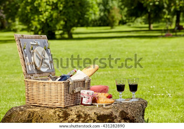 Fitted stylish wicker picnic hamper with red wine in wineglasses, jam and fresh bread on a rock in a sunny lush green park with copy space