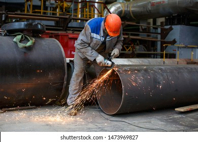 Fitter processes pipe edge with electric hand grinder