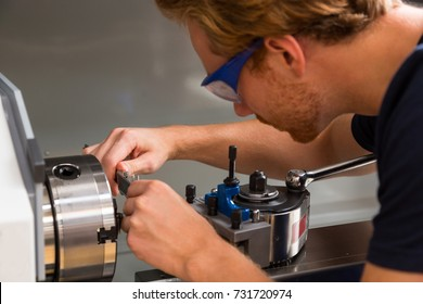 Fitter working at a turning machine in metal workshop
