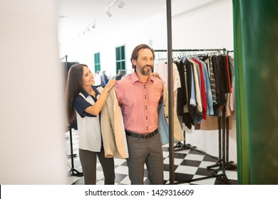 Fitting process. Smiling beaming radiant bewitching showroom consultant helping a dark-haired bearded attractive client during fitting a beige blazer.