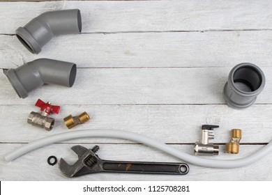 Fittings, pipe, valves, plastic pipe for water, adjustable wrench on the wooden background. Top view. Copy space for text