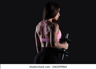 Fittness woman does the exercises with dumbbells on black background. Photo of muscular woman in sportswear on black background.