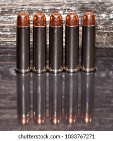 Five .357 magnum bullets lined up with a wooden background and on a reflective surface showing the bullets.
