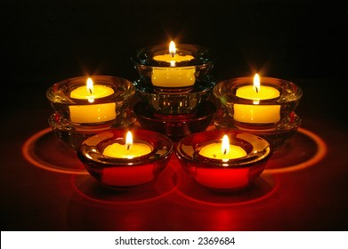 Five (5) tealight candles in glass holders arranged in three levels at night.