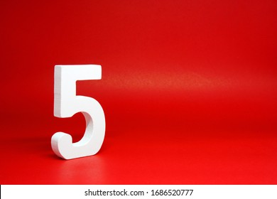 Five ( 5 ) white number wooden Isolated Red Background with Copy Space - New promotion 5% Percentage  Business finance Concept
