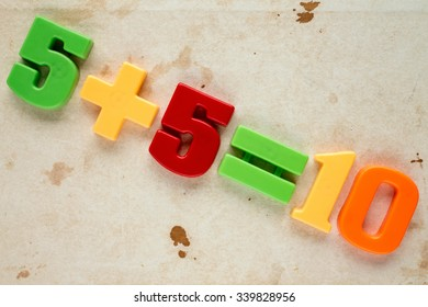 Five add five, simple math addition on old canvas background