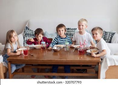 Five adorable kids, eating spaghetti at home, having fun
