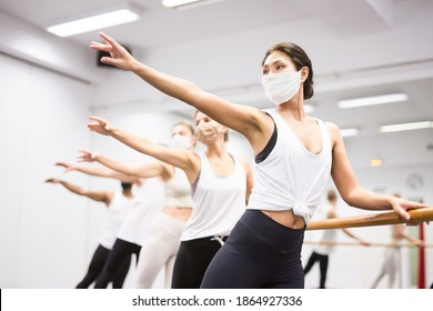 Five aduls people doing exercises on stretching ballet barre during COVID-19 .pandemic.