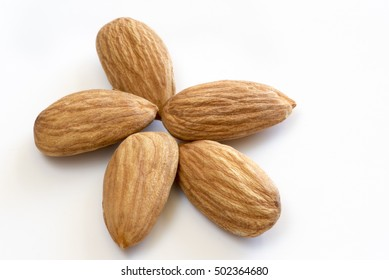 Five Almond nuts forming a star on a white surface. The almond seed comes from the Prunus dulcis or Prunus amygdalus which is a species of tree native to the Middle East