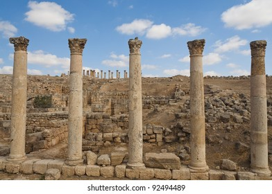 Five ancient vertical columns with capstones along the Roman road in Jerash, Jordan
