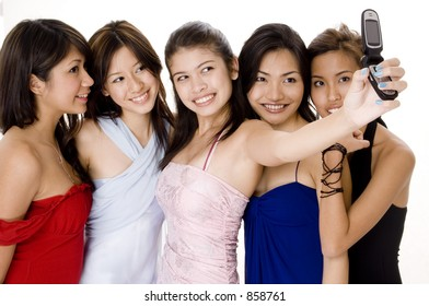 Five attractive young asian women in evening wear take their photo using a camera phone
