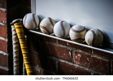 Five baseballs sitting by two bats in an old brick dugout