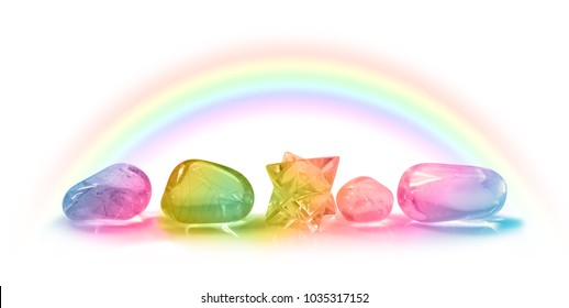 Five Beautiful Rainbow Healing Crystals - Four rainbow colored healing crystals and a merkabah laid in a row on a white background with a rainbow arcing above from left to right