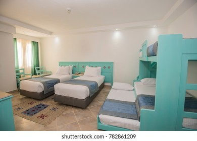 Five beds in family room of a luxury hotel resort with bunks.