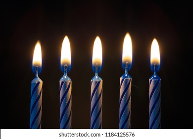 Five birthday candles isolated on black background