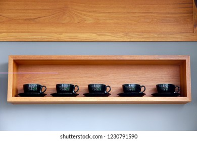 Five black latte cups in a wooden shelf on the wall. The decoration in a coffee shop. The abstract concept of relax life style or tea time at office.