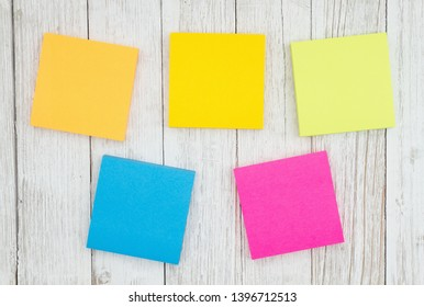 Five blank sticky notes on weathered whitewash textured wood background you can use as a mockup for your message
