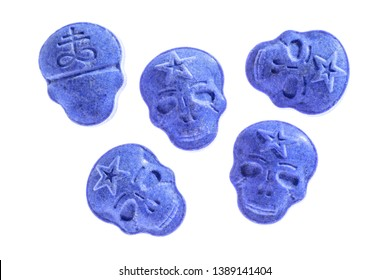 Five blue army Skull, Ecstasy, MDMA, Amphetamine or medication pills shaped like a skull isolated on a white background.